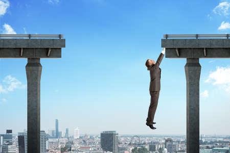 Zakenman opknoping uit van de kapotte brug boven de stad scape Stockfoto
