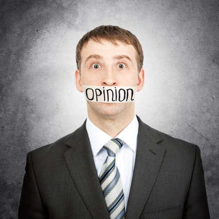 boca cerrada: Hombre de negocios con cinta adhesiva sobre su boca con la opinión palabra aislada en el fondo blanco