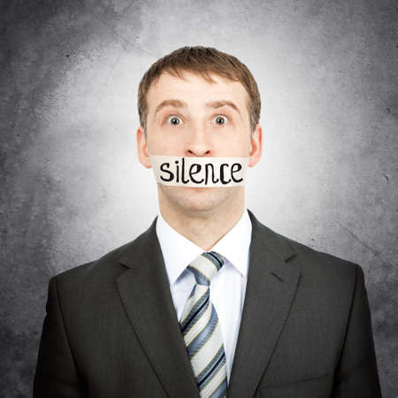 word of mouth: Businessman with tape over his mouth with word silence isolated on white background Stock Photo