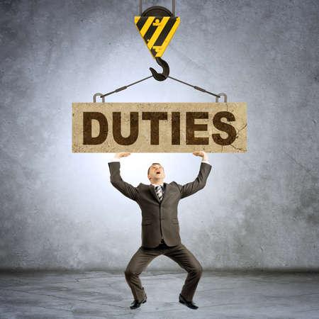 duties: Businessman holding heavy word duties on grey wall background
