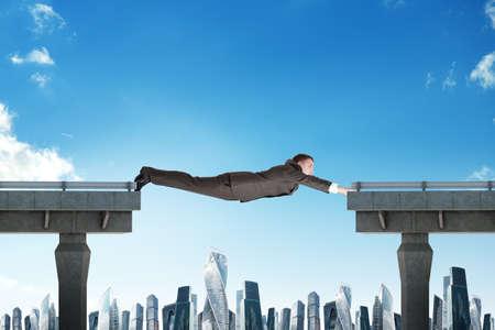 Geschäftsmann verbindet kaputte Brücke über der Stadt scape