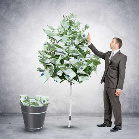 bucket of money: Businessman collecting money from tree with bucket full of money Stock Photo