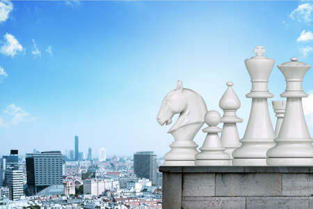 Set of white chessmen on roof of building with cityscape