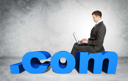 dot com: Businessman working on laptop and sitting on word dot com on grey wall background