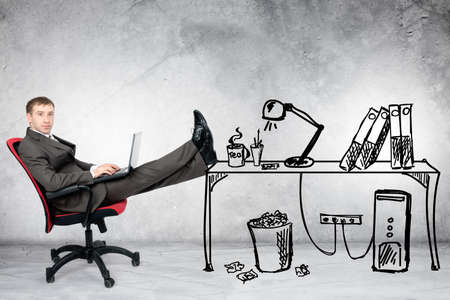 legs up: Businessman sitting on chair with legs up and laptop with drawn office