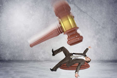 Inscribed gavel hitting scared businessman on grey wall background, justice concept