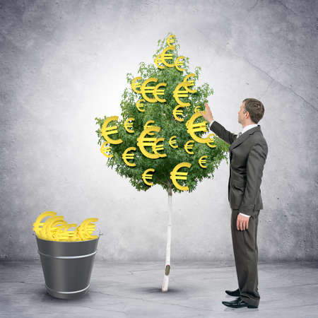 bucket of money: Businessman collecting euro signs from tree with bucket full of dollars, easy money concept