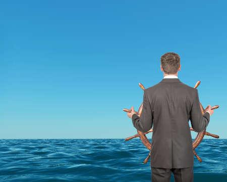 Geschäftsmann hält Lenkrad mit blauem Meer, Reise-Konzept