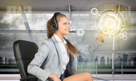 businesslady: Smiling businesslady touching holographic screen, technology concept