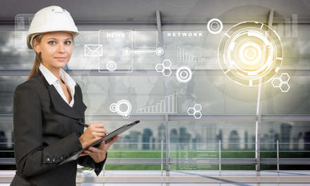 businesslady: Smiling businesslady in helemet lookingat camera, technology concept