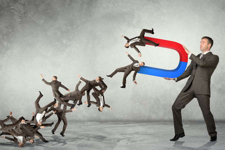 Businessman catching people within magnet on grey wall background, business concept 写真素材