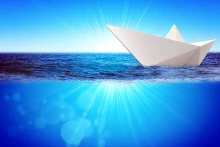 paper boat: Origami paper boat in blue sea and blue sky