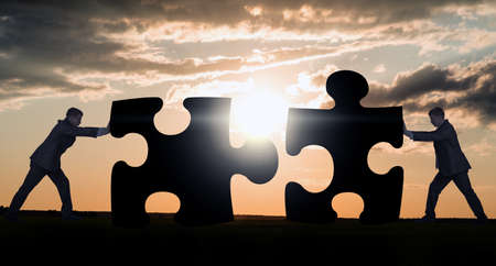 combining: Two businessmen combining big pieces of puzzle
