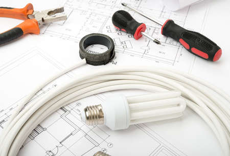 cabel: Architecture plan and rolls of blueprints with bulbs and screwdrivers. Building concept