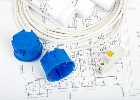cabel: Architecture plan and rolls of blueprints with cabel and blue plastic covers, closeup. Building concept