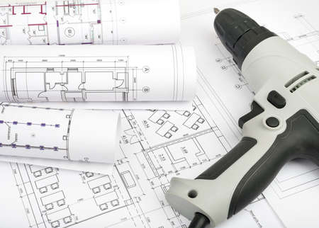 cabel: Architecture plan and rolls of blueprints with electric screwdriver. Building concept