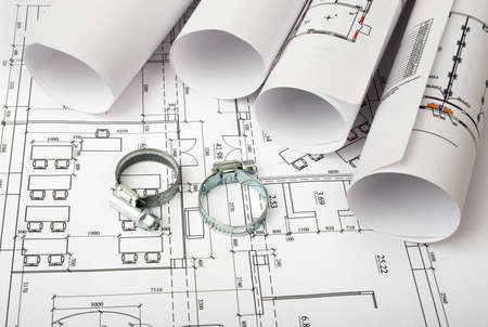 rounds: Architecture plan and rolls of blueprints with iron rounds. Building concept Stock Photo