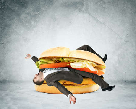 adult sandwich: Businessman inside hamburger on grey wall background