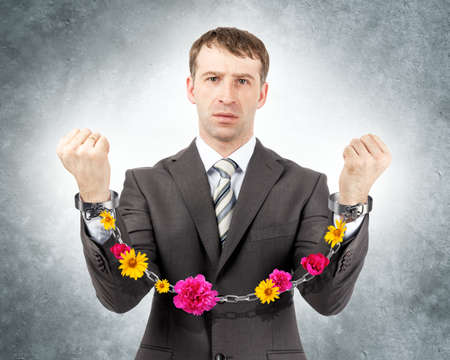 cuffs: Businessman in cuffs with flowers on grey wall background