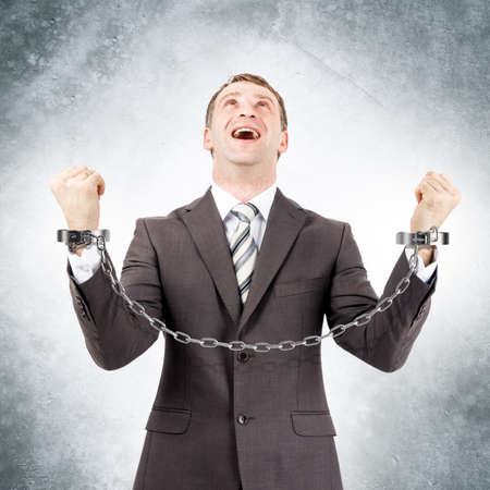 cuffs: Happy businessman in cuffs on grey wall background Stock Photo