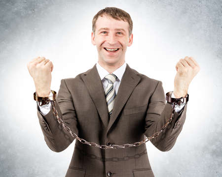 cuffs: Happy businessman in cuffs looking at camera on grey wall background
