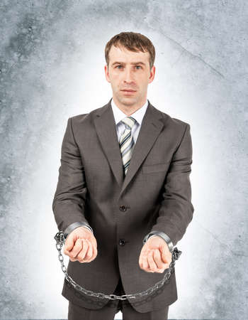 cuffs: Angry businessman in cuffs on grey wall background