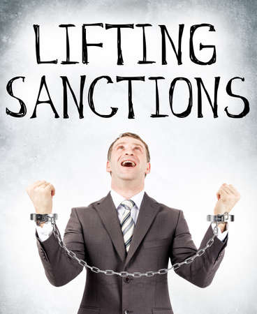hand cuff: Happy businessman in cuffs looking at lifting sanctions on grey wall background