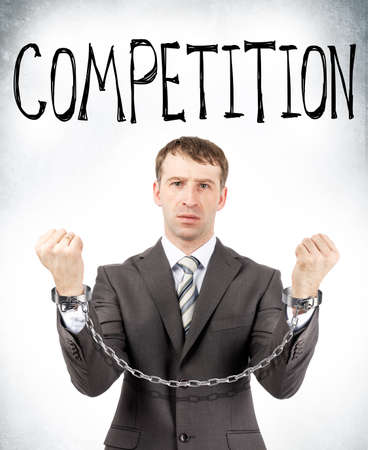 hand cuff: Businessman in cuffs with competition word on grey wall background Stock Photo