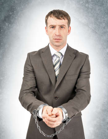 cuffs: Serious businessman in cuffs on grey wall background Stock Photo