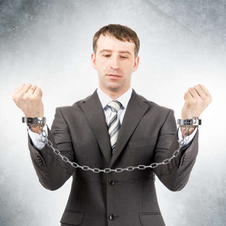 cuffs: Businessman looking at cuffs on grey wall background