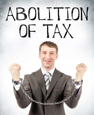 cuffs: Happy businessman in cuffs with abolition of tax on grey wall background Stock Photo