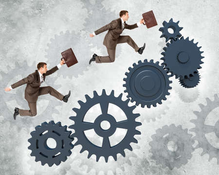 two wheel: Two businessmen running fast on wheel gears on grey wall background
