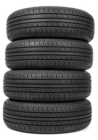Stack of four new black tyres. Isolated on white background
