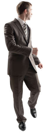 Full length portrait of young business man walking while looking back, away from the camera isolated on white background