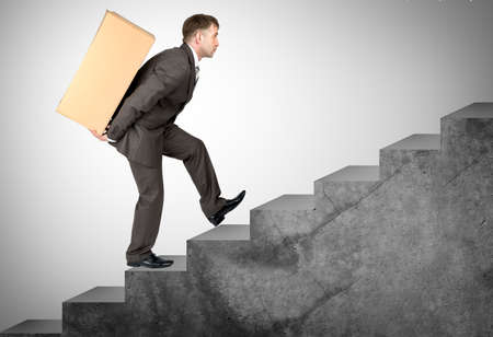 difficult task: Middle aged business man with difficult task going up stairs Stock Photo