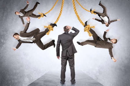 powerless: Confused businessman looking on hanging people on rope Stock Photo