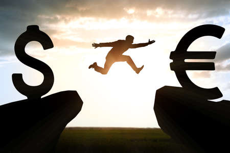 abyss: Businessman hopping over abyss from dollar to euro