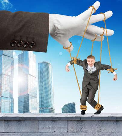 obedecer: Imagen de hombre de negocios que cuelgan en cadenas como marioneta. La fotografía conceptual