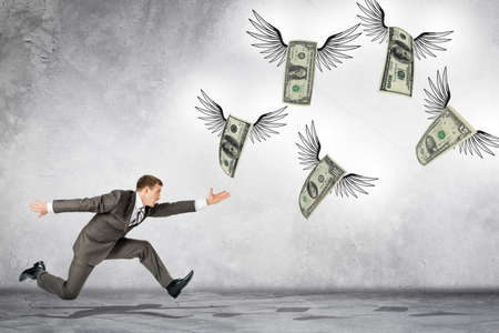 flying man: Business man running to catch flying dollars on gray background