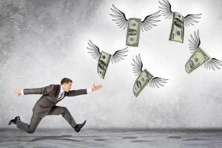 pagando: hombre de negocios corriendo para la captura de dólares que vuelan sobre fondo gris
