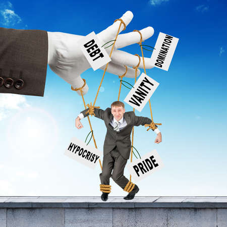 glove puppet: Image of businessman hanging on strings like marionette with words. Conceptual photography