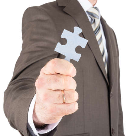 innovator: Businessman or innovator holding blank puzzle piece towards you isolated on white background