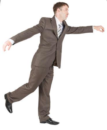 apologetic: Businessman balancing on one leg isolated on white background Stock Photo