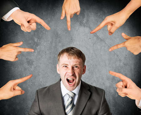 reprimand: Many fingers pointing at screaming stressed businessman on grey background