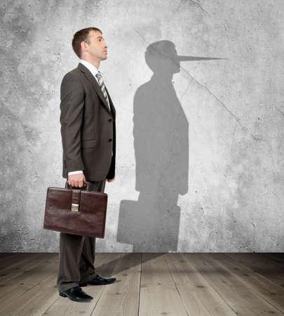 Hombre de negocios con una larga nariz en su sombra