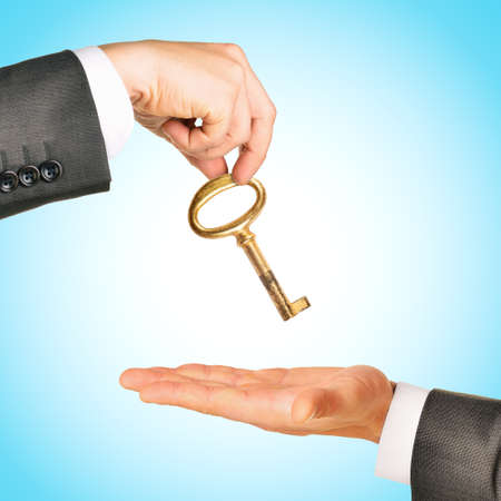gold key: Gold key exchange between two businessmen on blue