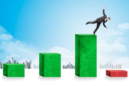 economic crisis: Businessmen falling down toward economic crisis on city background