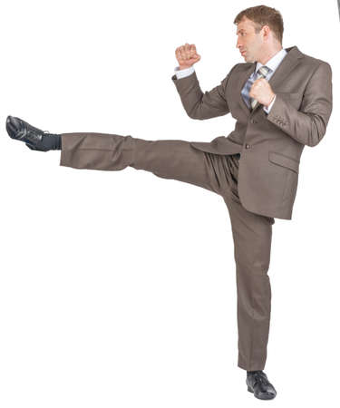 Angry businessman kicking isolated on white background Imagens