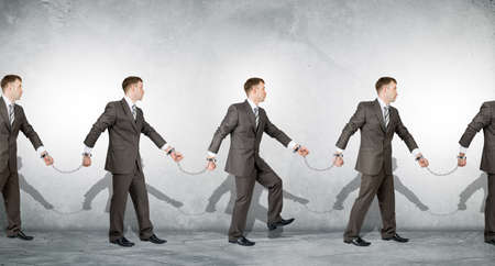 white collar crime: Businessmen in handcuffs arrested on grey background Stock Photo
