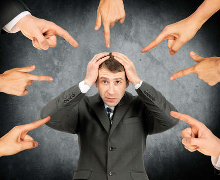 Shamed businessman with set of fingers pointing at him
